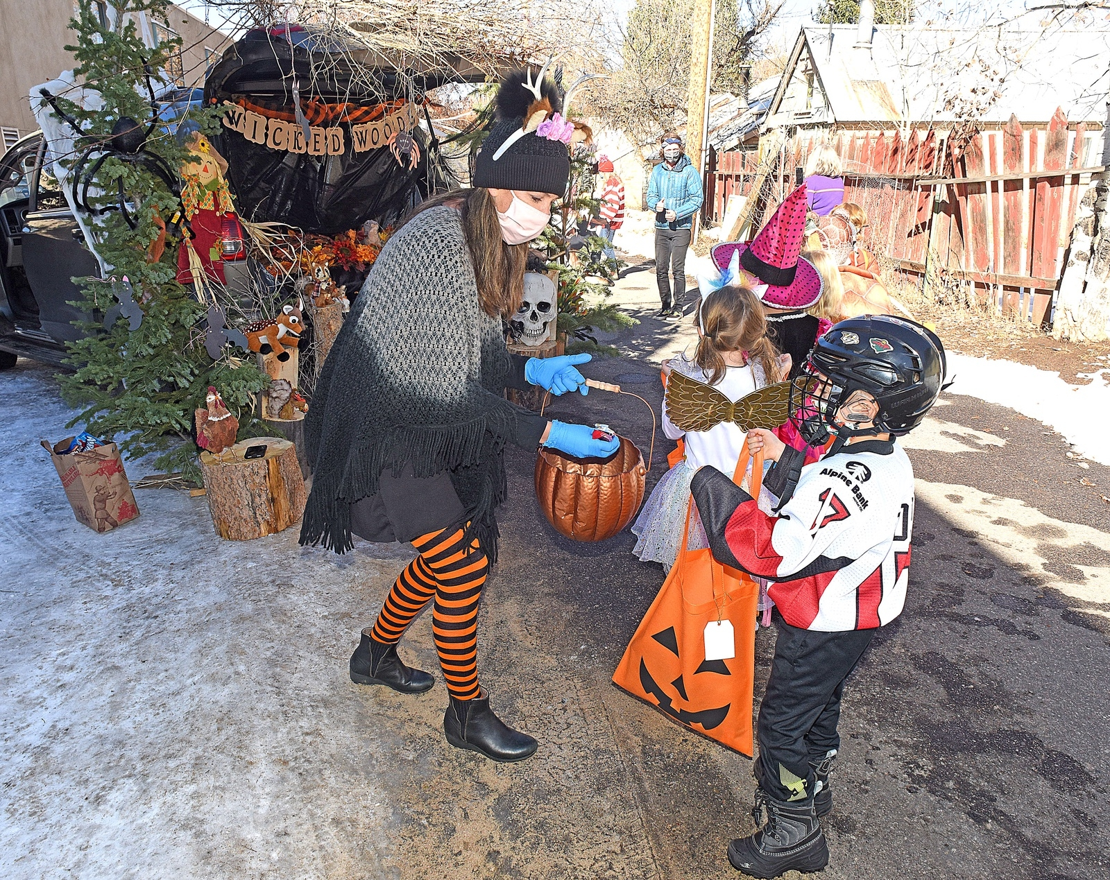 Chelsea McCarthy hands out candy to Baxter Ross at Emerald Mountain School look on Friday morning. The event was held outdoor with each class taking a turn at visiting distanced Halloween stands where teachers and portents safely handed out treats to the costumed children who were all wearing protective masks.