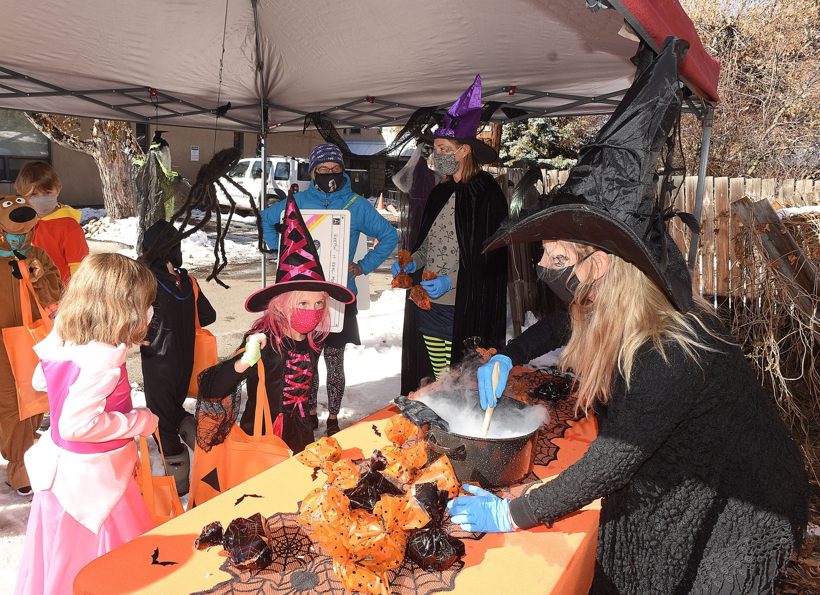 Tinisha Meader stirs her witches brew as first graders at Emerald Mountain School look on Friday morning. The event was held outdoor with each class taking a turn at visiting distanced Halloween stands where teachers and portents safely handed out treats to the costumed children who were all wearing protective masks.