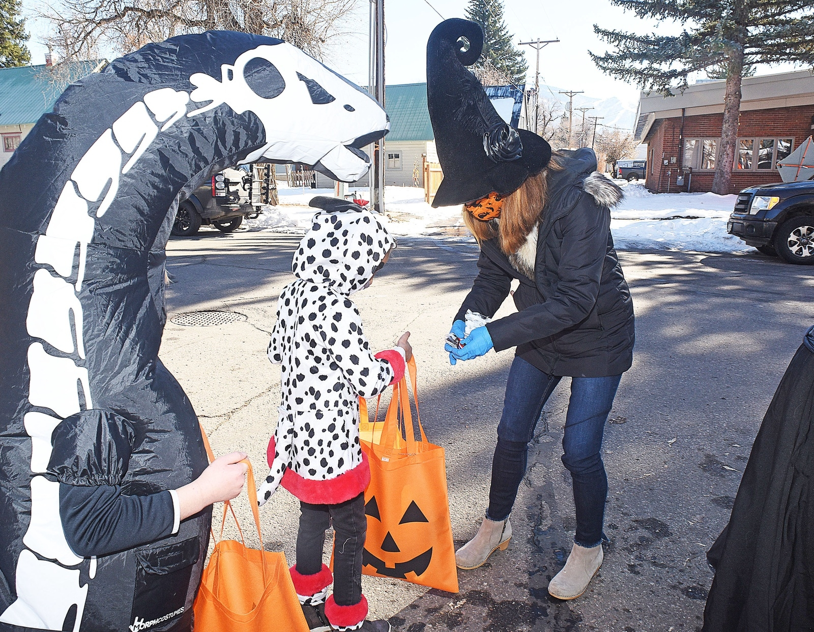 Jennifer Grathwohl hands out candy at the Emerald Mountain School's trick or treat event Friday morning in the alley way outside the school. The event was held outdoor with each class taking a turn at visiting distanced Halloween stands where teachers and portents safely handed out treats to the costumed children who were all wearing protective masks.